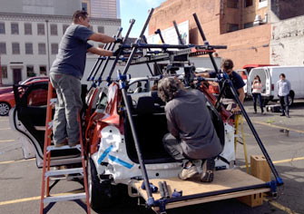 Rear view of two 6-foot linking mini Sliders rigged on a car to hold an underslung camera
