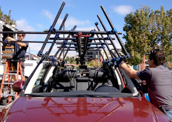 Front view of two 6-foot linking mini Sliders rigged on a car to hold an underslung camera